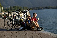 Germany, Bavaria, Tegernsee, Couple with mountain bikes eating ice cream - DSF00018