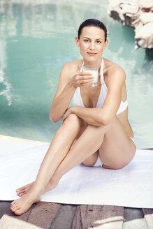 Young woman in bikini holding a glass of milk - ABF00440