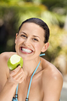 Young woman in bikini holding apple, smiling, close-up - ABF00434