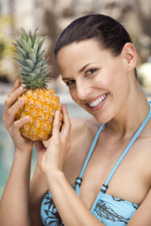 Young woman in bikini holding ananas, portrait - ABF00427