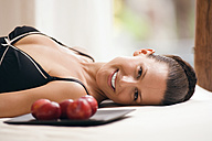 Young woman wearing neglige, relaxing on bed alongside tray with plums - ABF00420