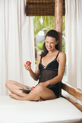 Young woman wearing neglige, sitting on bed alongside tray with plums - ABF00417