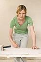 Young woman renovating, preparing wallpaper, portrait - WESTF09172
