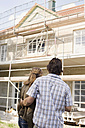 Couple Looking at New Home Construction, rear view - WESTF09149