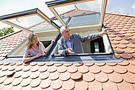Couple looking out dormer  windows, man pointing - WESTF09079
