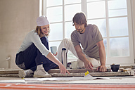 Young couple sitting on floor of empty room, examining plans - WESTF09067