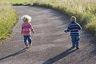 Little girl (2-3) and boy (1-2) running across path, rear view - SMOF00148