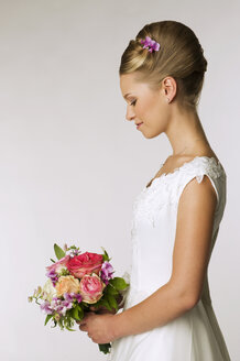 Young bride holding bridal bouquet, side view - NHF00887