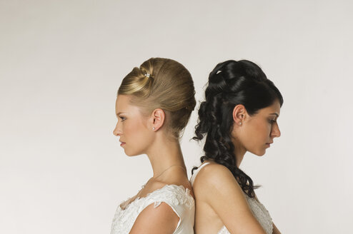 Young brides standing back to back, portrait - NHF00884