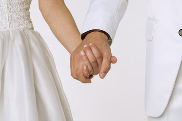 Bride and groom holding hands, mid section, close-up - NHF00870
