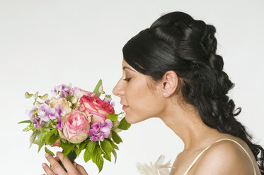 Young bride smelling flowers, side view, close-up - NHF00843