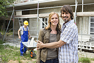 Young couple at site embracing, construction worker in background - WESTF09152