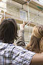Young couple at construction site, rear view, close-up - WESTF09137