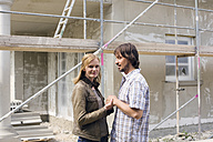 Young couple in front of home under construction - WESTF09133
