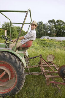 Farmer on tractor ploughing field - BMF00500