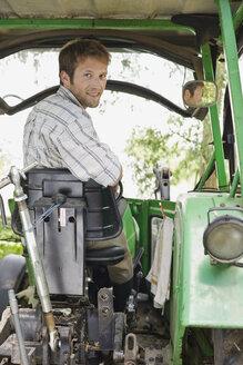 Farmer sitting on tractor - BMF00434