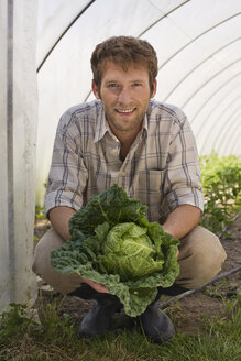 Man in greenhouse holding cabbage, portrait - BMF00425