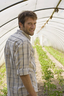 Man in greenhouse, smiling, portrait - BMF00422