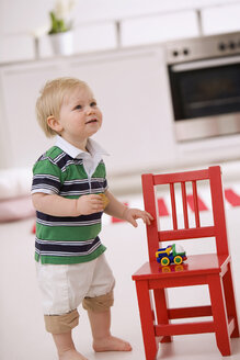 Baby boy (1-2) playing with red chair - SMO00371