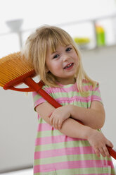 Little girl (4-5) playing with broom, portrait, close-up - SMO00344