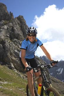 Germany, Bavaria, Karwendel, Woman mountain biking - MRF01099