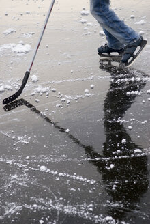 Person playing ice hockey on frozen lake - AWDF00295