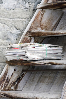 Pile of newspapers on wooden staircase, close-up - AWDF00153