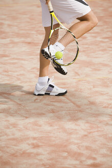 Male tennis player holding tennis racket, low section - UKF00156