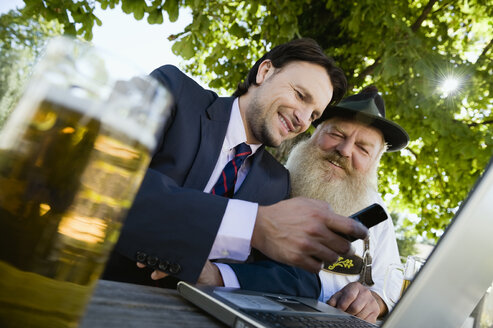 Germany, Bavaria, Upper Bavaria, Senior Bavarian man and young businessman with laptop in beer garden - WESTF09704