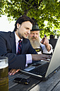 Germany, Bavaria, Upper Bavaria, Senior Bavarian man and young businessman with laptop in beer garden - WESTF09701
