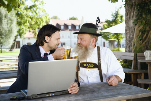 Germany, Bavaria, Upper Bavaria, Senior Bavarian man and young businessman with laptop in beer garden - WESTF09698