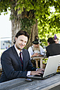Germany, Bavaria, Upper Bavaria, Young business man in beer garden using laptop, smiling, portrait - WESTF09692
