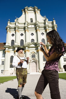 Germany, Bavaria, Upper Bavaria, Asian woman taking picture of Bavarian man with camera phone - WESTF09686
