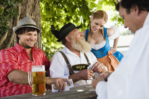 Germany, Bavaria, Upper Bavaria, People in beer garden playing cards - WESTF09647