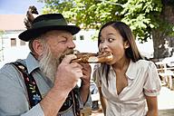 Germany, Bavaria, Upper Bavaria, Bavarian man and Asian woman in beer garden eating pretzel, portrait - WESTF09638