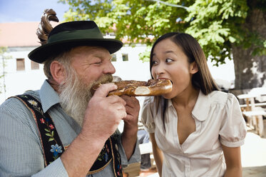 Germany, Bavaria, Upper Bavaria, Bavarian man and Asian woman in beer garden eating pretzel, portrait - WESTF09638
