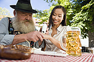 Germany, Bavaria, Upper Bavaria, Bavarian man and Asian woman in beer garden, Asian woman testing a spot of snuff - WESTF09635