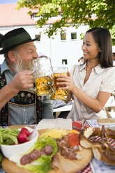 Germany, Bavaria, Upper Bavaria, Asian woman and bavarian man toasting each other - WESTF09625