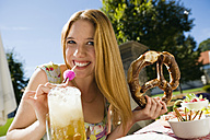 Germany, Bavaria, Upper Bavaria, Young woman in beer garden, smiling, portrait - WESTF09598