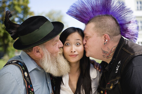 Germany, Bavaria, Upper Bavaria, Two men kissing Asian woman on cheek, portrait - WESTF09550