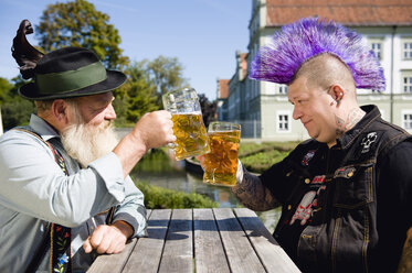 Germany, Bavaria, Upper Bavaria, Man with mohawk hairstyle and Bavarian man holding beer stein glasses - WESTF09541