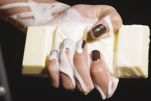 Female hand holding melting chocolate bar, close-up - OW00882