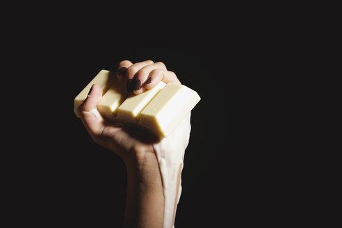 Female hand holding melting chocolate bar, close-up - OW00879