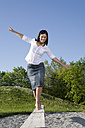Young woman balancing on boardwalk in a playground - CLF00613
