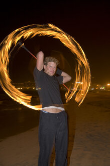 Spain, Canary Islands, Gran Canaria, Young man juggling with torches - PK00299