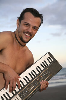 Spain, Canary Islands, Gran Canaria, Young man playing keyboard - PK00296