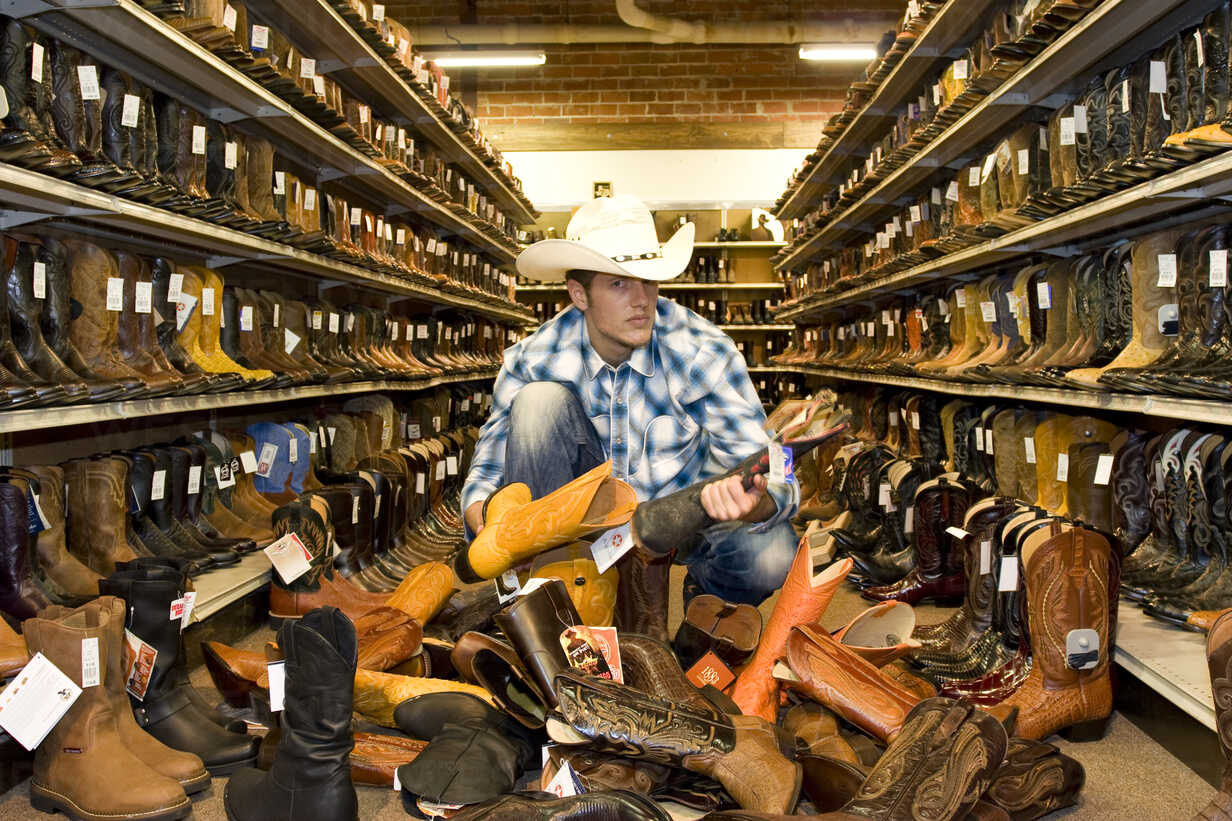 USA, Texas, Dallas, Young man choosing cowboy boots in shoe store - PK00243 - Phillip Koschel/Westend61