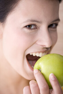 Young woman holding an apple, smiling, portrait - MAEF01214