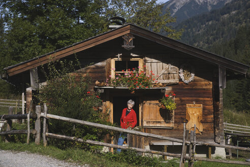 Austria, Karwendel, Senior woman standing in front of log cabin, smiling - WESTF10505