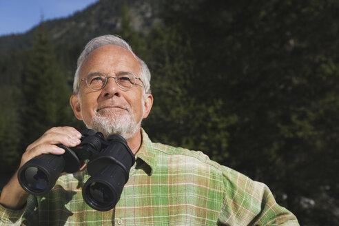 Austria, Karwendel, Senior man holding binocular, portrait - WESTF10499
